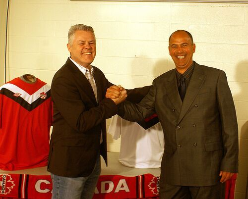 Umbro Canada president Gerald Woodman, left, shakes hands with national team coach Stephen Hart.