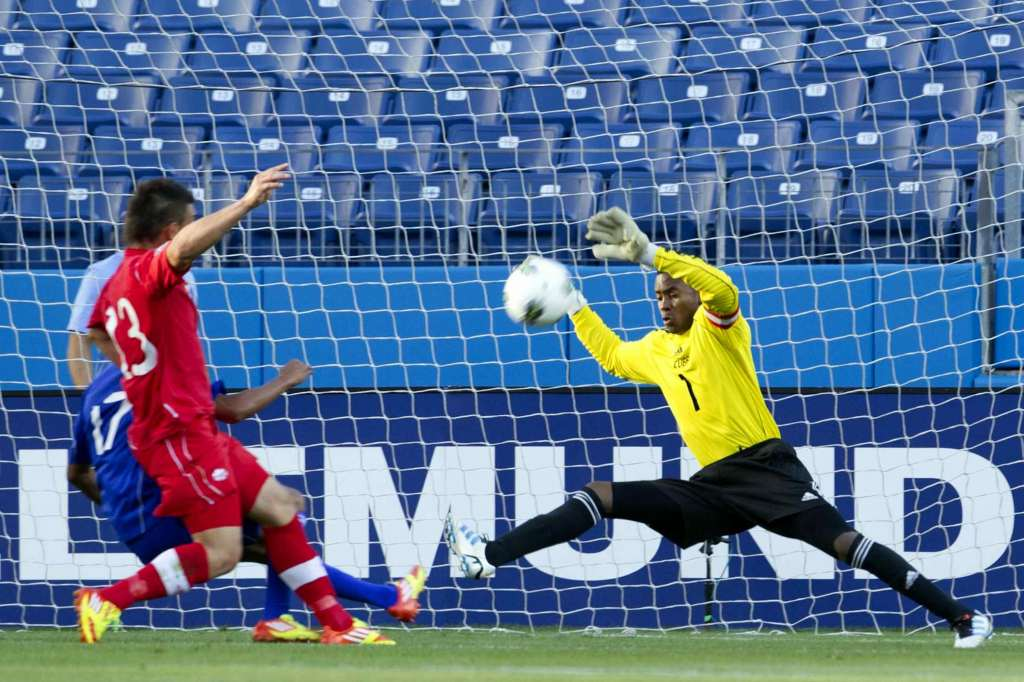 Cuba's Odinsel Cooper gets his hands up on a shot from Canada's Lucas Cavallini. PHOTO: CANADA SOCCER/MEXSPORT/ISAAC ORTIZ