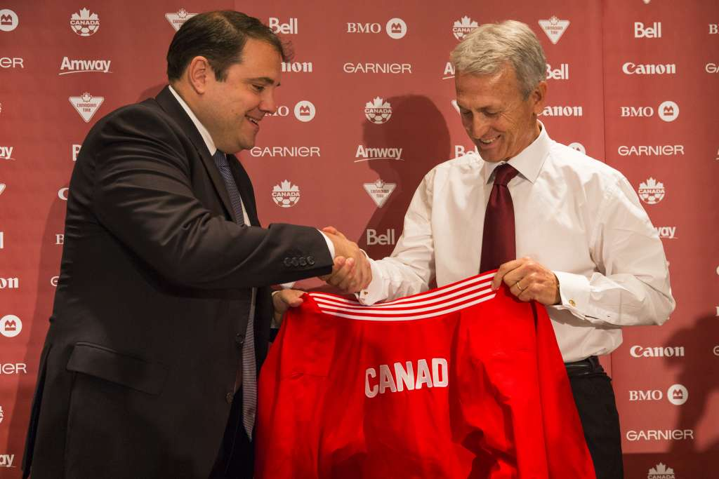 Victor Montagliani, left, hands new coach Benito Floro a Canadian jacket. PHOTO: CANADA SOCCER/PAUL GIAMOU