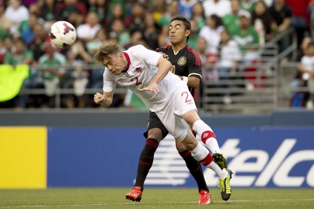 Canada's Nik Ledgerwood heads the ball away from Mexico's Marco Fabian. PHOTO: MEXSPORT/CANADA SOCCER