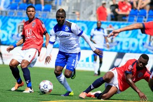 FC Edmonton's Horace James, centre, skips by Indy's Kleberson, left. PHOTO: FC EDMONTON/TONY LEWIS