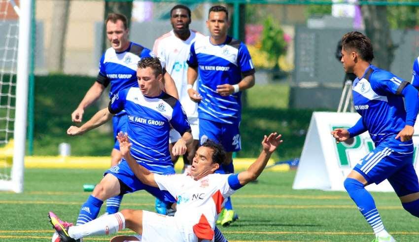 Carolina's Omar Bravo is challenged by FCE's Nik Ledgerwood. PHOTO: TONY LEWIS/FC EDMONTON