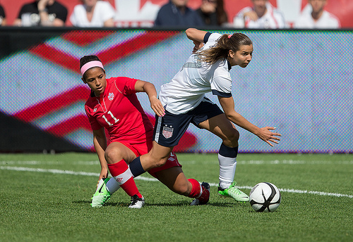 Canada's Desiree Scott, left, tries to challenge American Tobin Heath. PHOTO: CANADA SOCCER/PAUL GIAMOU