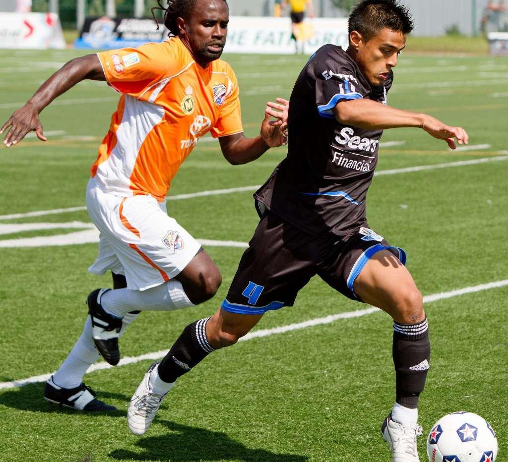 Puerto Rico's Osei Telesford, in orange, chases FCE's Serisay Barthelemy PHOTO: FC EDMONTON