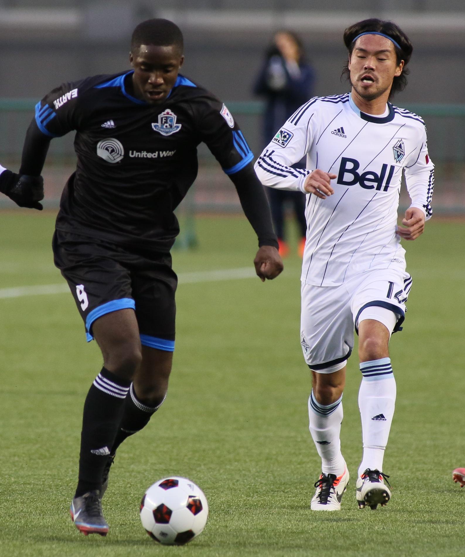 FCE's Michael Cox passes Whitecap Daigo Kobayashi. PHOTO: TONY LEWIS/CANADA SOCCER