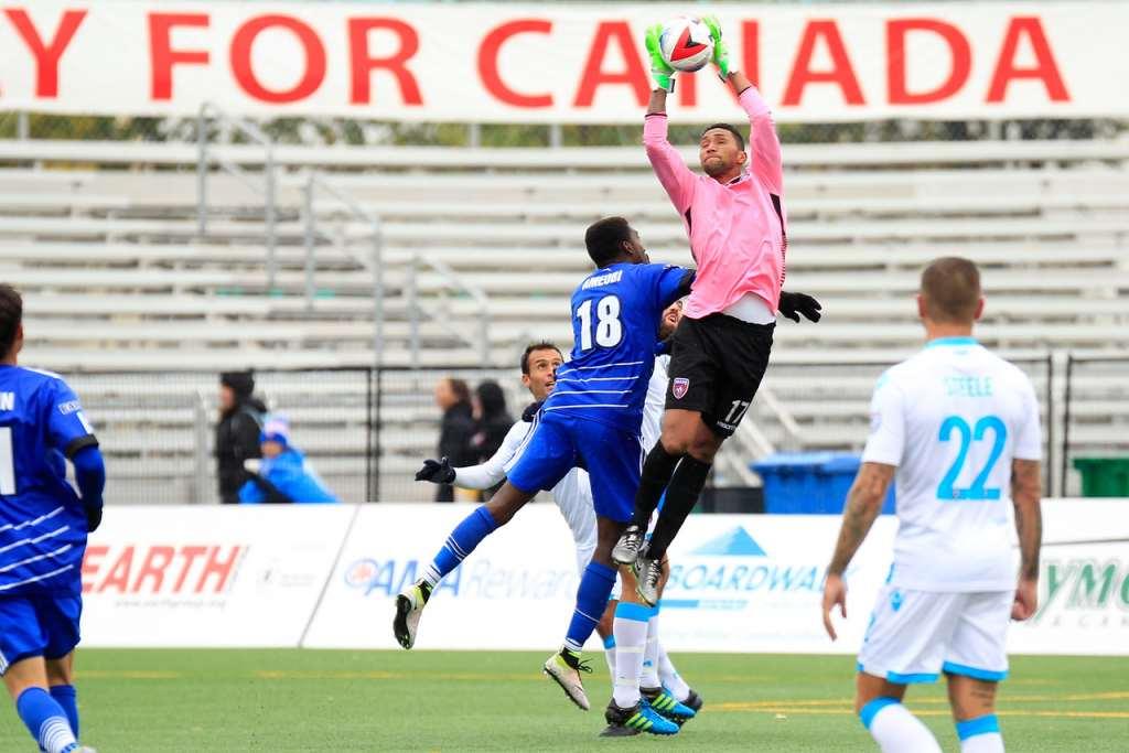 Miami goalkeeper Daniel Vega grabs the ball as he's challenged by FCE's Tomi Ameobi. PHOTO: TONY LEWIS/FC EDMONTON